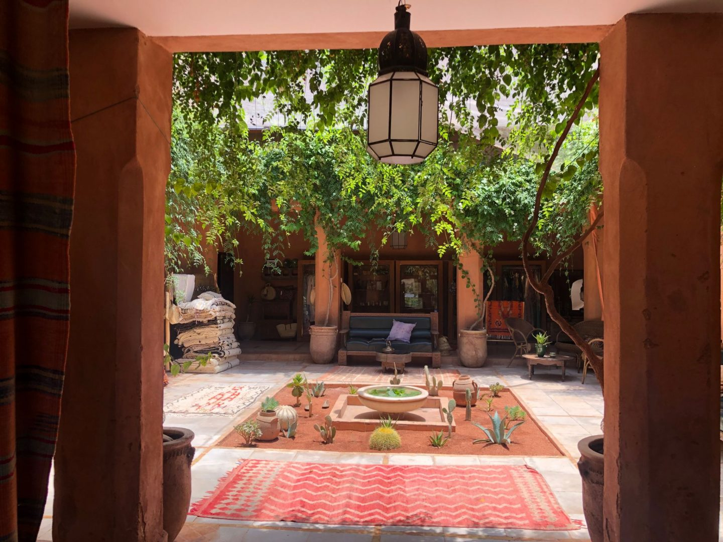 Entrance courtyard decorated with a selection of carpets, cushions and pottery etc