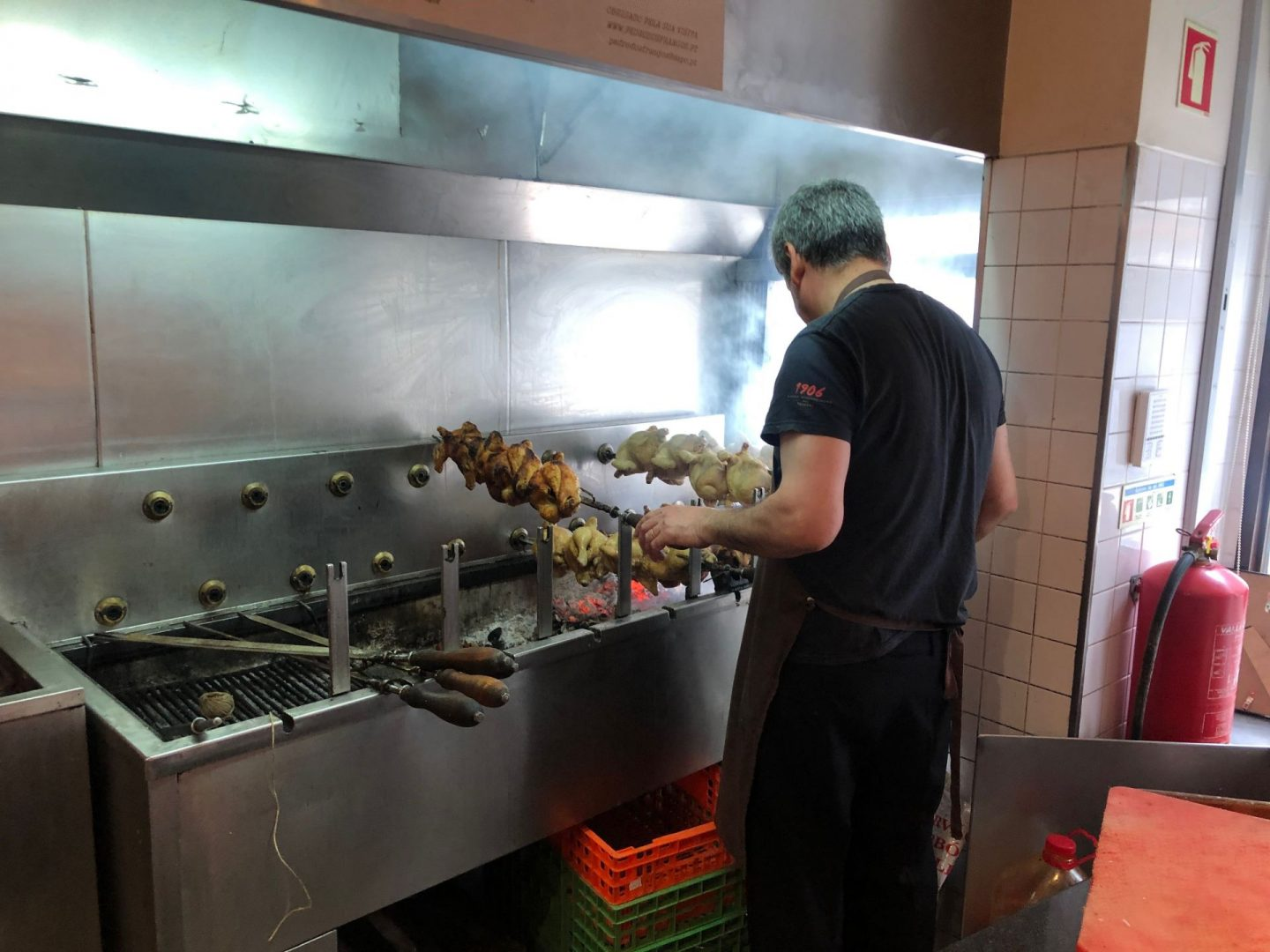 A man roasting chicken on a spit at Restaurante Pedro dos Frangos