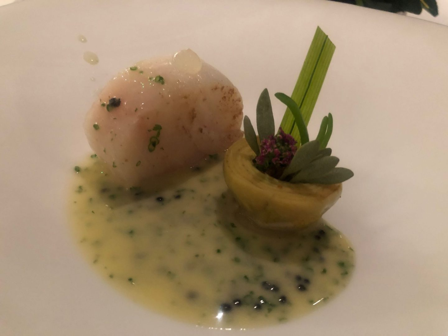Cod fillet poached in butter with a lemon gel , violet artichokes and a champagne sauce with caviar .