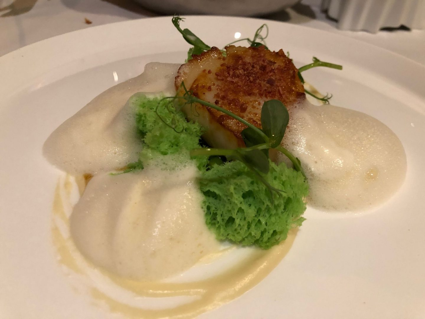 Seared scallop , fresh peas , Parma ham and Kampot pepper foam